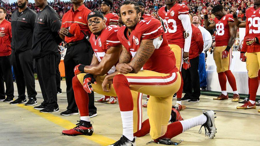 Colin Kaepernick (right) kneeling next to his teammate, Eric Reid (left).