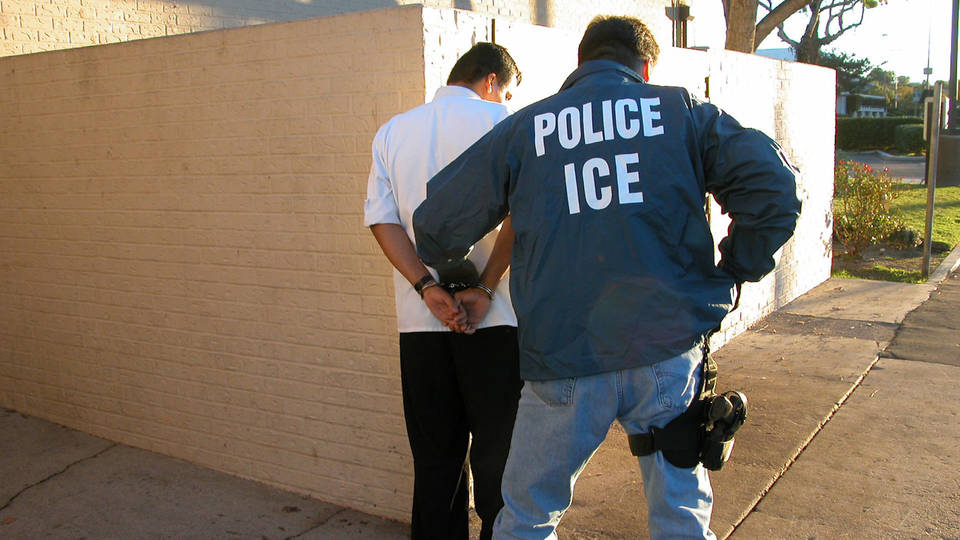 An ICE police officer arrests a man known to be an illegal immigrant outside his house in Pasadena, CA